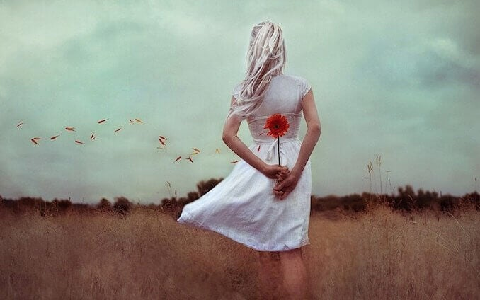 Donna di spalle che tiene un fiore dietro alla schiena