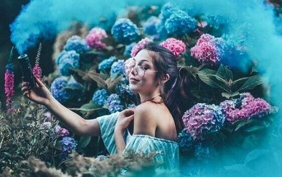 Ragazza in mezzo ai fiori mentre pensa che non bisogna dimostrare nulla