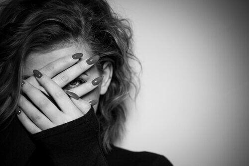 Donna che si copre il viso con una mano