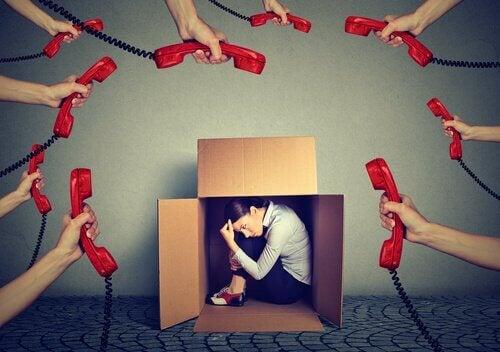 Donna nascosta in una scatola e circondata di telefoni