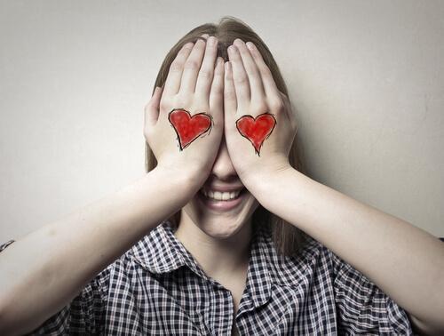 Donna si copre gli occhi con le mani e ha due cuori disegnati sui dorsi