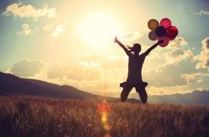Donna che salta con dei palloncini buttarsi