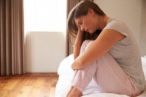 Donna preoccupata seduta sul letto