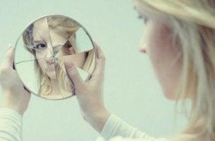 Donna che si guarda in uno specchio rotto