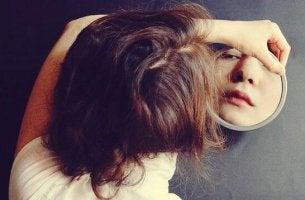 Donna che si guarda allo specchio sintomi della tristezza
