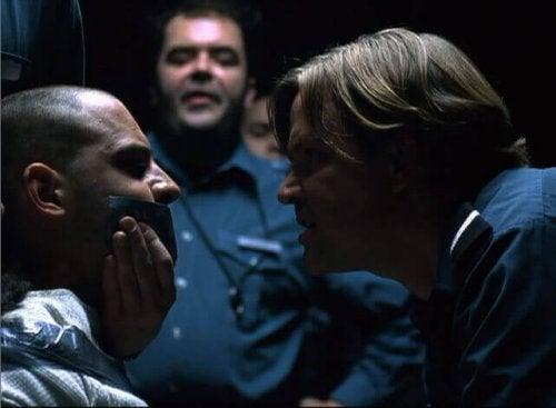 Guardia che tappa la bocca a un prigioniero