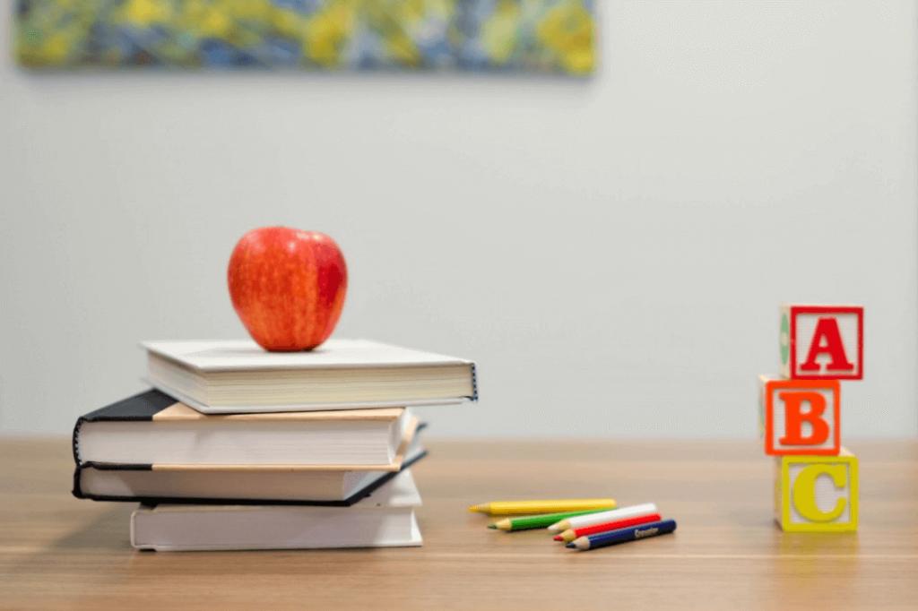 Libri, mela e pastelli