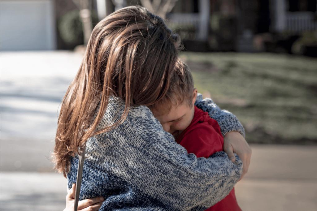 Madre che abbraccia suo figlio disabile