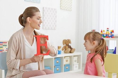Mamma mostra una lettera alla sua bambina che impara a parlare