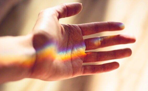 Mano con fascio di luce arcobaleno tollerare l'incertezza