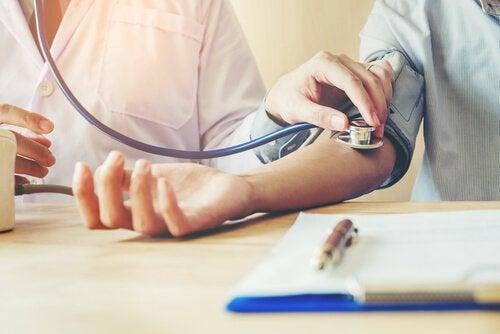 Medico che misura pressione arteriosa al suo paziente