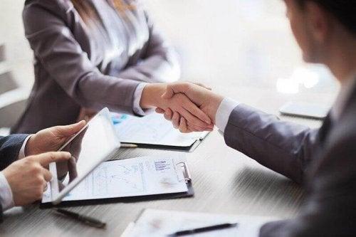 Recruiter e candidato si stringono la mano durante un colloquio di lavoro