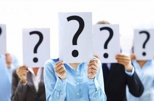 Persone con fogli con punti interrogativi