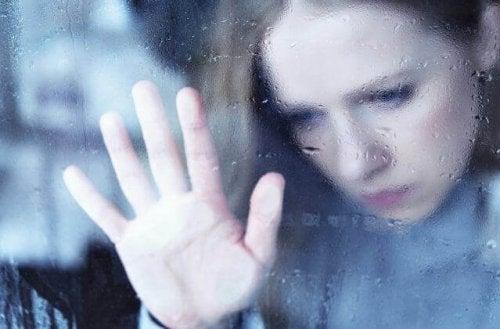 Ragazza dietro alla finestra mentre fuori piove