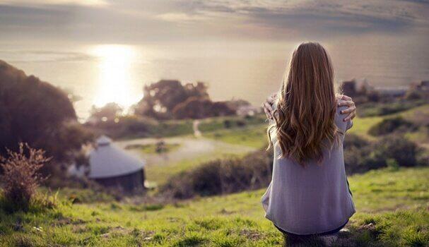 Ragazza seduta di spalle di fronte al mare
