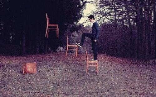 Ragazzo che sale su sedie sospese in aria
