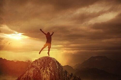 Uomo che salta sulla cima di una montagna