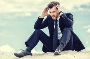 Uomo con un completo seduto sulla sabbia con le mani tra i capelli