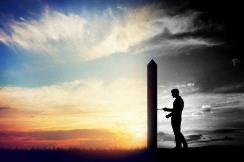 Uomo dietro a porta che divide luce da ombra perché affronta le sue paure