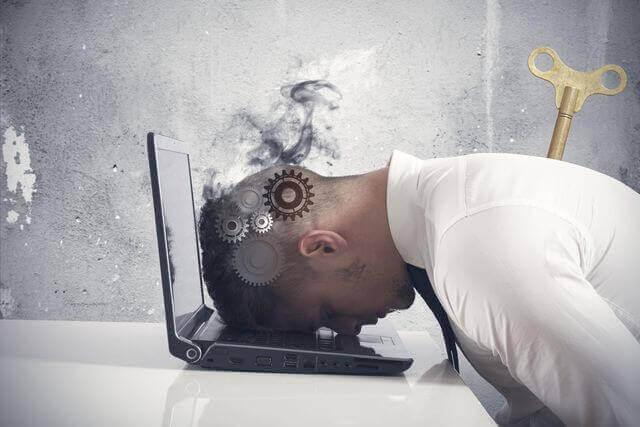 Uomo esaurito con testa su tastiera computer distrutti dal lavoro