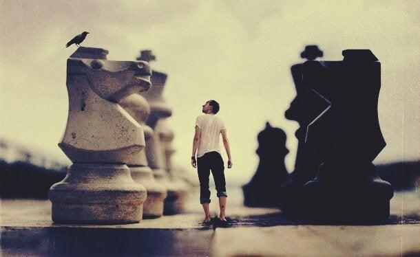 Uomo tra pezzi degli scacchi giganti scoprire la personalità altrui