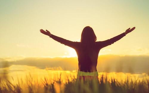 Ottimismo e salute, donna con le braccia al cielo