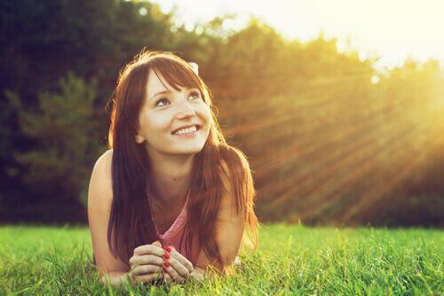 Ottimismo e salute, ragazza guarda il sole e sorride