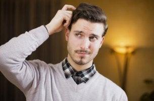 Un uomo si gratta la testa il linguaggio del corpo