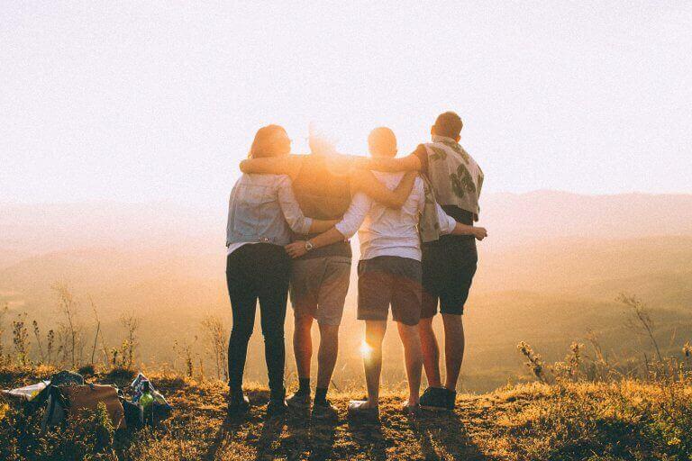 Amici abbracciati in cima a montagna
