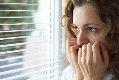 Angoscia, donna impaurita alla finestra