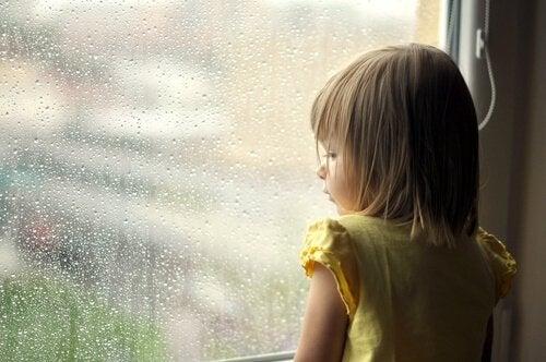 Bambina superdotata che guarda dalla finestra