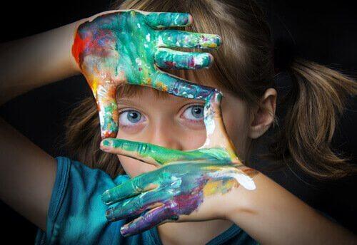 Bambina con mani colorate