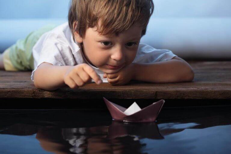 Bambino con barchetta di carta che persegue i suoi sogni