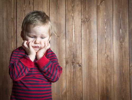 Bambino frustrato con parete in legno dietro