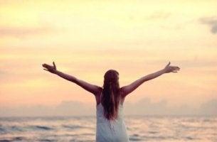 Donna con braccia aperte approfittare al massimo di ogni giorno