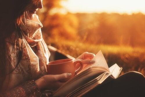Donna che beve caffè e legge un libro