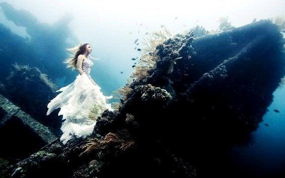 Donna che cammina verso alto sott'acqua