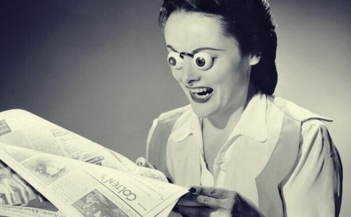 Donna che legge giornale con occhi fuori da orbite