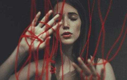 Una donna avvolta da fili rossi