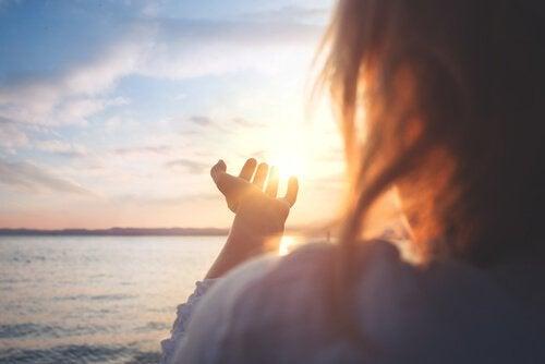 Donna in riva al mare che guarda il sole