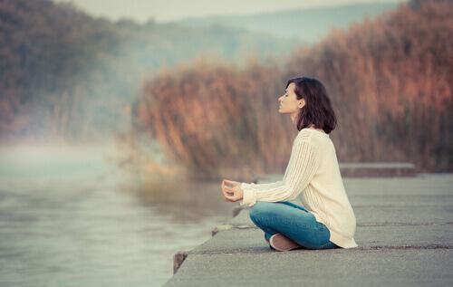 Donna medita al lago gestire lo stress