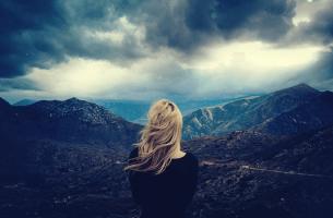 Donna che guarda delle montagne e pensa alle caratteristiche delle persone autodistruttive