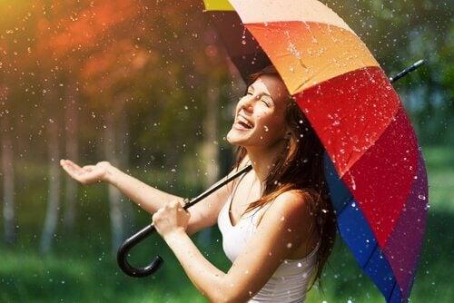 Donna sorridente con ombrello sotto a pioggia essere felici