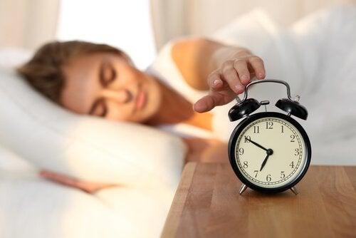 Donna spegne la sveglia svegliarsi già stanchi