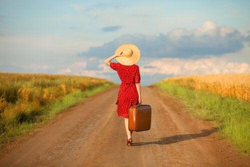 Donna su strada sterrata con valigia