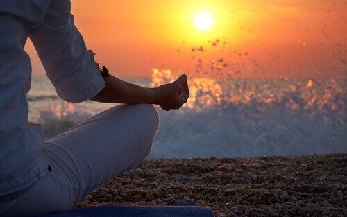 Donna in posizione yoga sulla spiaggia