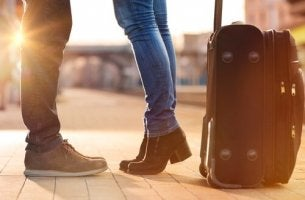 Gambe di due partner con valigia