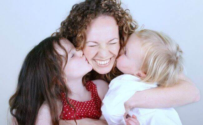 Madre sorridente abbracciata a figli