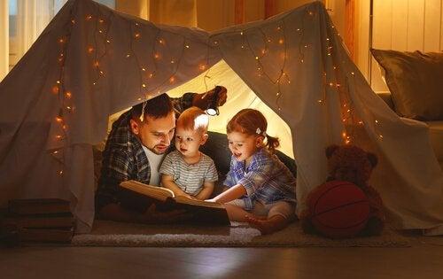 Papà che legge con i suoi bambini dentro a una tenda
