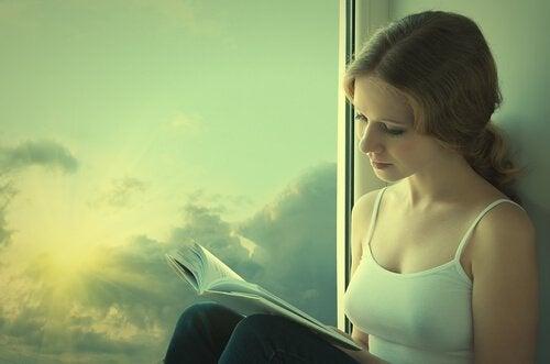 Ragazza che legge accanto a finestra
